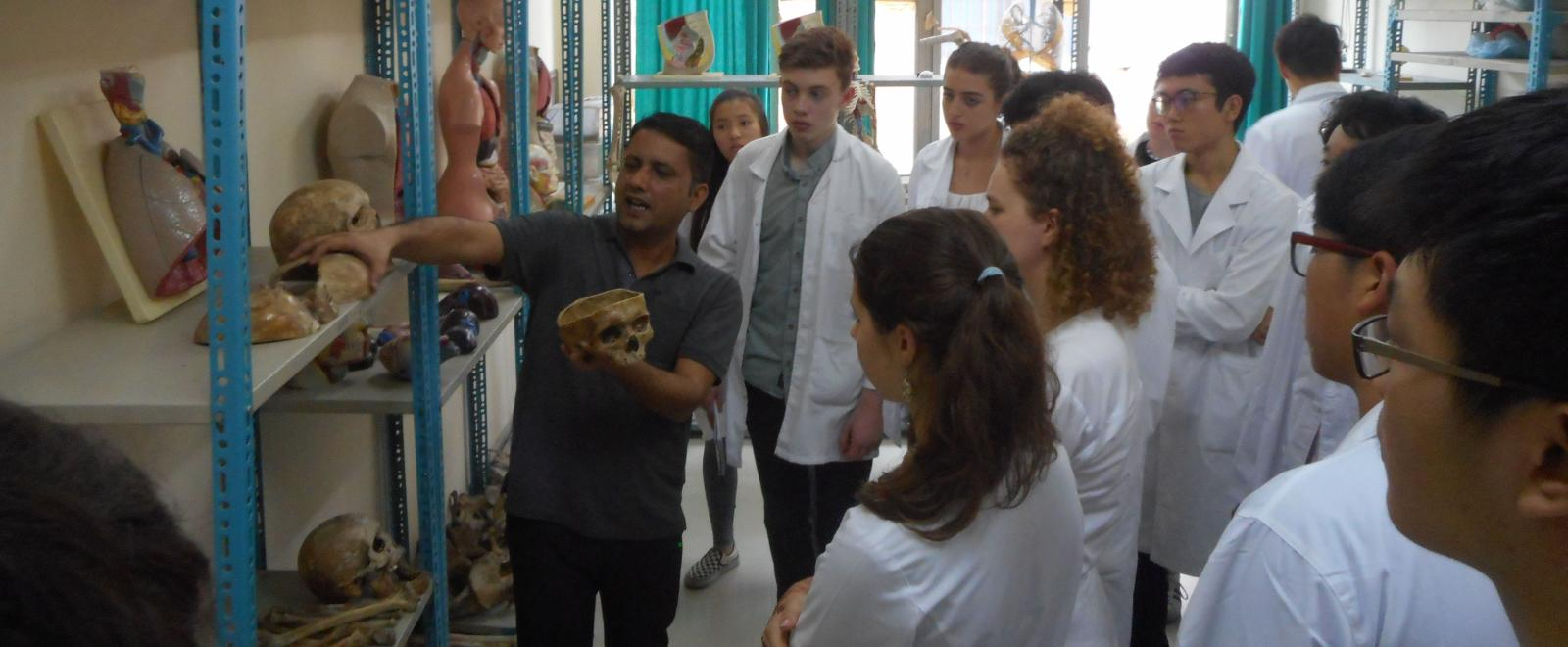 Medical interns listen to a doctor as he teaches them anatomy during their team trip in Nepal